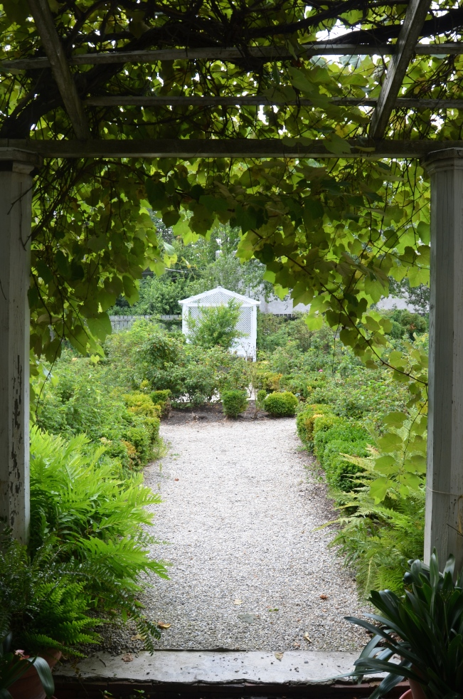 "The view from ""The Garden Door"" at Wyck. Looking towards the box edged rose garden and to the simple white arbor containing a shady sitting place."