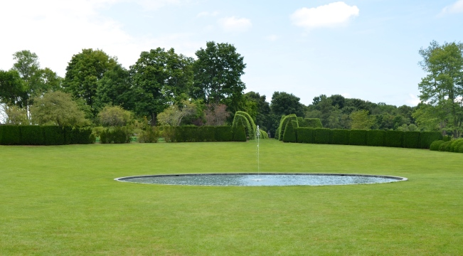 A tranquil oval pool reflects the sky in the center of the Great Bowl at Ladew Topiary Garden
